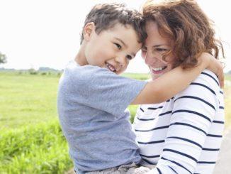 Mother hugging son on rural road