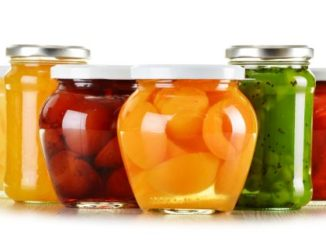 Jars with fruity compotes and jams isolated on white background. Preserved fruits